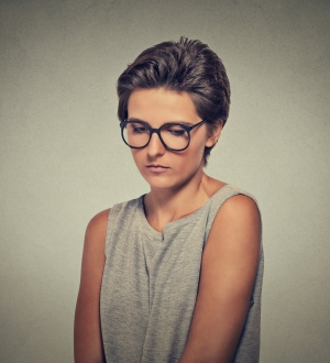 Lack of confidence. Shy woman in glasses feels awkward