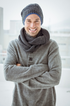Handsome man in warm clothing smiling at camera