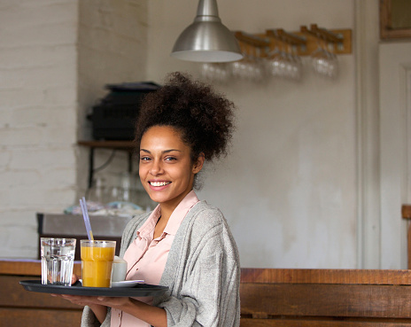Smiling waitress holding tray of drinks in restaurant